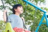 Asian Little Boy Having Fun On A Swing In Beautiful Summer Garden On Warm And Sunny Day Outdoors. As poster