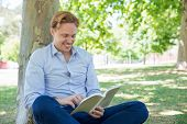 Joyful Handsome Guy Reading In Park. Handsome Man In Shirt Sitting On Grass, Leaning On Tree, Holdin poster
