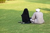 stock photo of burka  - islamic woman in burka sitting on the green with her husband - JPG
