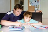 Cute Little School Kid Boy At Home Making Homework With Dad. Little Child Writing With Colorful Penc poster