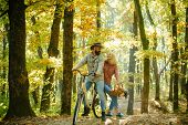Couple In Love Ride Bicycle Together In Forest Park. Romantic Date With Bicycle. Bearded Man And Wom poster