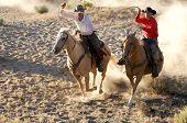 stock photo of buckaroo  - Two Cowboys galloping and roping through the desert - JPG