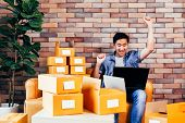 Young Asian Happy Male Business Entrepreneur Using Computer Laptop While Packing Products Into Boxes poster