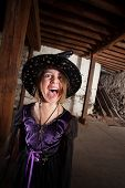 stock photo of sceptre  - Screaming young female witch with hat and purple dress - JPG