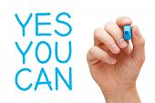 stock photo of slogan  - Yes You Can and hand holding blue marker - JPG