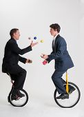 stock photo of unicycle  - Two businessmen juggle six different colored balls between them while riding unicycles - JPG