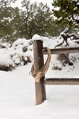 stock photo of wrangler  - A wrangler lasso draped over a fence post in a snowy - JPG
