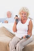 Постер, плакат: Пожилая женщина подъем гантели на кровати