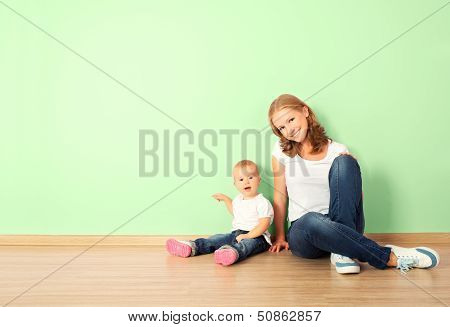Happy Family Of Mother And Child Sitting On The Floor In An Empty Wall poster