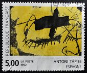 A stamp printed in France shows an abstract painting by Antoni Tapies