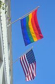 stock photo of queer  - A gay pride and American flag against a blue sky - JPG