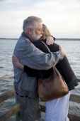 Older Couple Hugging On Dock