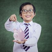 stock photo of japanese coin  - Happy boy puts the coin into a piggy bank on chalkboard background - JPG