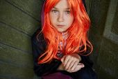 stock photo of antichrist  - Portrait of calm Halloween girl with red hair looking at camera - JPG