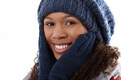 Closeup winter portrait of attractive ethnic woman with hands around face.