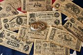 image of confederation  - assorted confederate money and belt buckle on confederate flag - JPG