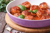 foto of meatball  - hot fresh meatballs with tomato sauce in a frying pan on a wooden table - JPG