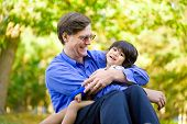 foto of disability  - Businessman holding his disabled son on grass - JPG