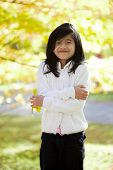image of biracial  - Little biracial asian girl standing amongst bright autumn leaves - JPG