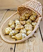 stock photo of jerusalem artichokes  - Jerusalem artichoke tubers in a wicker basket on a wooden boards background - JPG