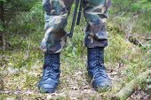 Soldier's legs in army boots in a forest