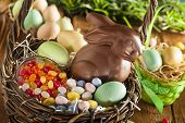 stock photo of candy  - Chocolate Easter Bunny in a Basket with Assorted Candy - JPG