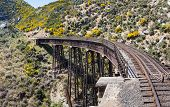 stock photo of ravines  - Railway track of Taieri Gorge tourist railway crosses a steel trestle bridge across a ravine on its journey up the valley