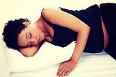 stock photo of baby bump  - Beautiful young pregnant woman lying on bed - JPG
