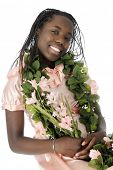 A beautiful tween girl dressed up in peach and adorned with leis of leaves and flowers.  On a white