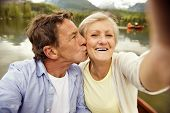 stock photo of life-boat  - Senior couple on boat with mountains in background taking selfie - JPG