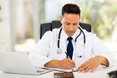 picture of medical office  - male medical doctor writing reports in his office - JPG