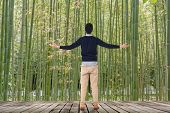 stock photo of bamboo forest  - Man standing and looking into the bamboo forest - JPG