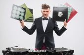 ������, ������: DJ in tuxedo showing his vinyl records standing by turntable