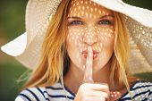 pic of shh  - Pretty woman in sunhat looking at camera and making shh gesture - JPG