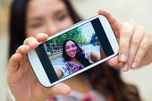 picture of selfie  - Outdoor portrait of pretty student girl taking a selfie.