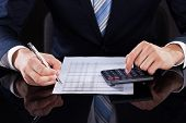 pic of financial audit  - Midsection of businessman calculating financial expenses at desk - JPG