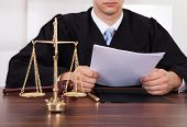 stock photo of courtroom  - Midsection of male judge reading document at table in courtroom - JPG