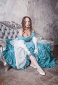 picture of tight dress  - Beautiful woman in blue medieval dress putting stockings on the sofa - JPG
