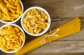 stock photo of pasta  - Different kinds of italian pasta like a fusilli farfalle spaghetti and penne pasta - JPG