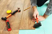 stock photo of laminate  - Carpenter worker installing laminate flooring in the room - JPG