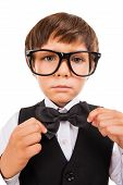 picture of little boys only  - Cute little boy adjusting his bow tie and looking at camera while standing isolated on white - JPG