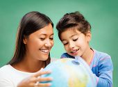 Постер, плакат: children education geography school and happy people concept happy teacher and girl with globe