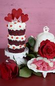 picture of red velvet cake  - Vintage style triple layer red velvet cupcake on white cake stand with roses and candy against a vintage shabby chic pink and red wood background. Vertical.