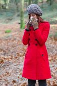 foto of overcoats  - Young woman suffering from a cold or flu blowing her nose on a white paper handkerchief on a forest wearing a red overcoat - JPG