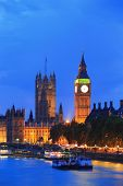 foto of london night  - Big Ben and Houses of Parliament with blur ships on thames river at night London United Kingdom UK - JPG