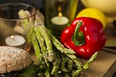 stock photo of spears  - Fresh green asparagus spears with red bell pepper lying on a wooden kitchen counter with lighted candles and fresh brown rolls - JPG