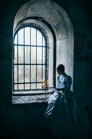 stock photo of dungeon  - Woman in victorian dress imprisoned in a dungeon - JPG