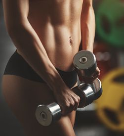 picture of body shapes  - Brutal athletic woman pumping up muscles with dumbbells - JPG
