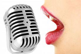 stock photo of karaoke  - Singing woman and retro microphone - JPG