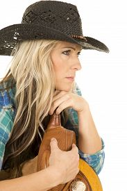 pic of western saddle  - A cowgirl looking to the side in her plaid shirt wearing her black western hat and laying on her saddle - JPG